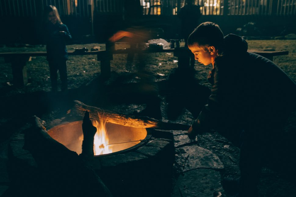 autism camps, child by a campfire